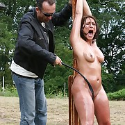 Oiled pussy and knockers getting lashed on outdoor pillory with full force