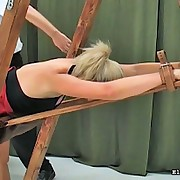 Girl in mini girl acquires bent over wooden device gets her acquisitive gazoo paddled
