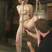 Nude slave is tied up to the pole