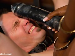 Pretty ebony pinches slave�s dick and fucks him with dildo