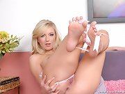 Barefoot blonde with big pierced tits gets her feet soaked in cum