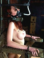 A heavy iron collar immobilizes redheaded beauty in bondage chair.