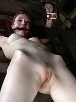 A heavy iron collar immobilizes redheaded beauty in bondage chair
