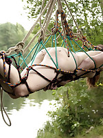 Sexy girl suspended from a tree like a spider's prey