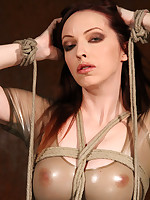 Brunette in translucent latex dress struggles in rope