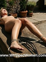 Woman tied down outdoors and flogged