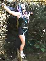 Catya has her hands manacles above her head and tied to a tree