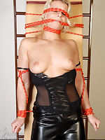 Blonde in leather pants is bound upright to board with rope