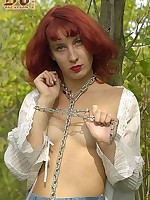Topless redhead chained to tree