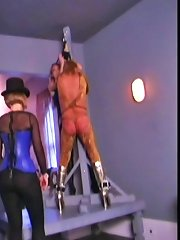 In the gothic dungeon the bitch is suspended upside down for some electric cbt