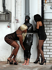 Tied to a post and wrapped in cling film the slave must endure a whipping from two Mistresses
