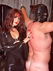 Gorgeous mistress in long latex dress trains two sissy slaves in her dungeon