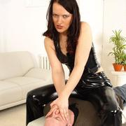 Domina in black latex smother slaveboy