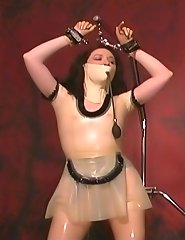 Latex slave suspended on handcuffs