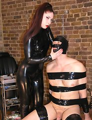 Mistress Lillith torments the taped down slave's nipples.