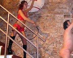 Mistress in orange latex punished slave
